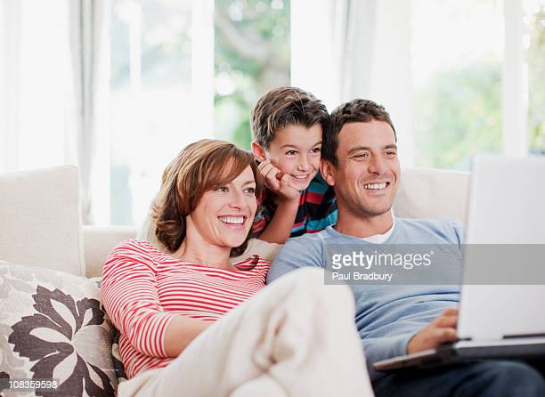 Family using laptop on sofa together