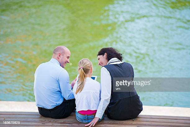Family Using Tablet Outdoors On A Bench