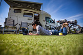 Woman next to a bicycle near the camper. Caravan car Vacation. Family vacation travel, holiday trip in motorhome
