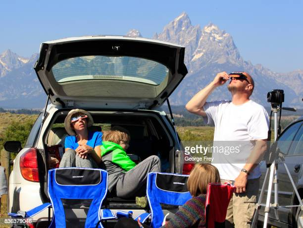 A family views the solar eclipse in the first phase of a total eclipse in Grand Teton National Park on August 21 2017 outside Jackson Wyoming...