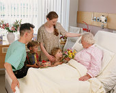 Family visiting elderly woman in hospital