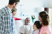 Family visiting happy man in hospital ward