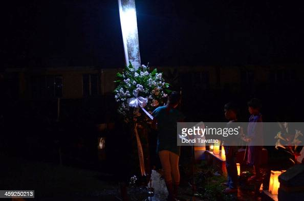 TACLOBAN LEYTE PHILIPPINES DECEMBER 24 A family visitsthe grave of a loved one who perished during Typhoon Haiyan at a flooded mass grave on...