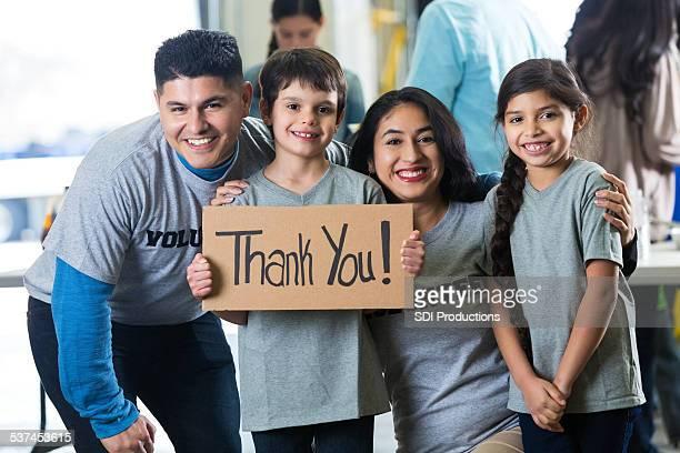 Família volunteering em conjunto e segurando sinal de agradecimento