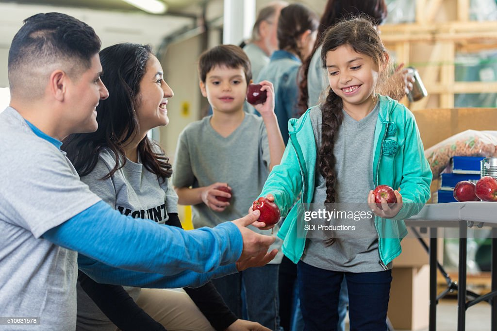 Family volunteers at food bank : Stock Photo