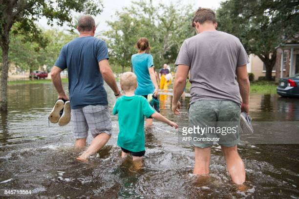 A family wades through the flooded streets of the San Marco historic district of Jacksonville Florida on September 11 after storm surge from...
