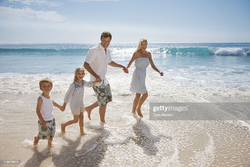 Family wading in ocean : Stock Photo
