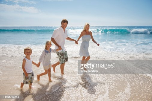 Family wading in ocean : Foto stock