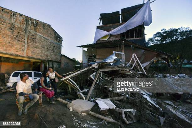TOPSHOT A family wait outside their home damaged by mudslides following heavy rains in Mocoa Putumayo department southern Colombia on April 1 2017...