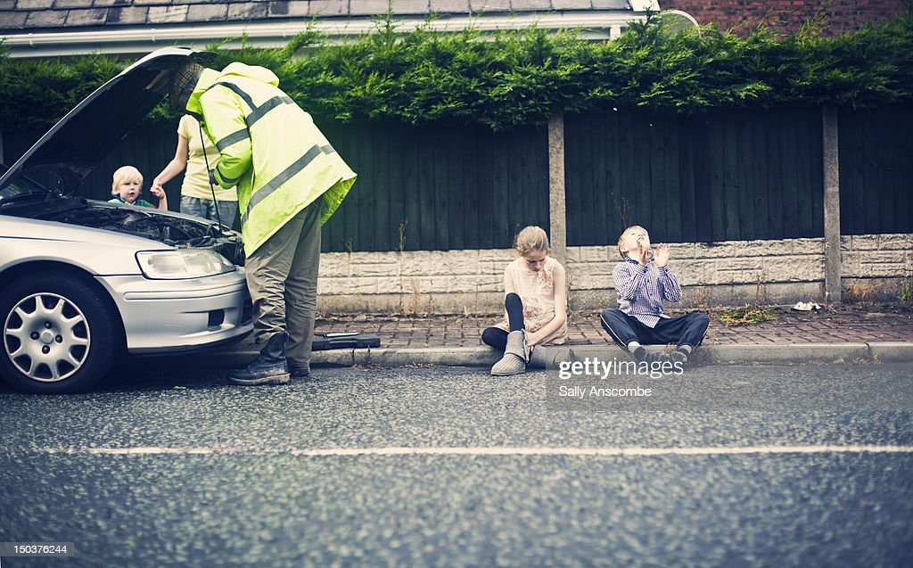 Family waiting for a broken down car to be fixed : Stock Photo