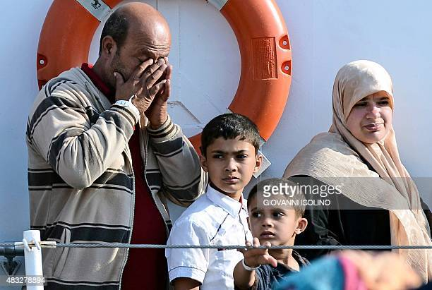 A family waits to disembark the patrol vessel Fiorillo of the Italian Coast Guard as it arrives in the port of Pozzallo on August 7 2015 after saving...