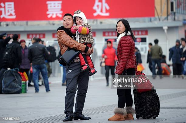 A family waits to take the train for the holidays at the entrance of the Beijing railway station on January 18 2014 The world's largest annual...