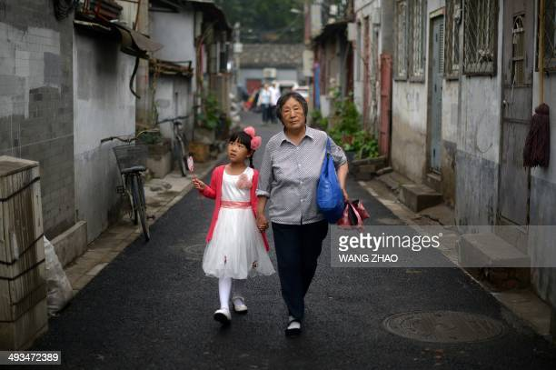 A family walk along an alley in Beijing on May 24 2014 Chinese manufacturing activity saw a sharp improvement in May hitting a fivemonth high HSBC...