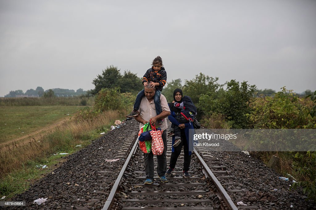 A family walk down rail tracks in the rain towards a pick up point taking refugees to a camp on September 10 2015 in Roszke Hungary Thousands of...