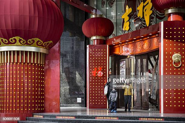 A family walk past festive decorations for Chinese New Year displayed outside a department store in Shanghai China on Sunday Jan 24 2016 For all the...