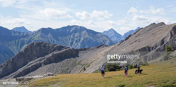 Family walk up alpine slope above mountains, valley