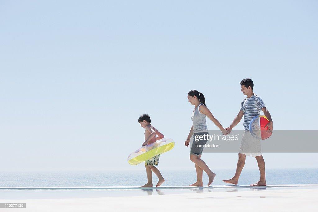 Family walking along infinity pool : Stock Photo