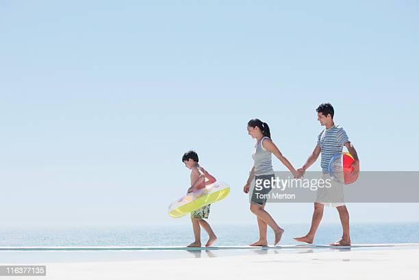 Family walking along infinity pool