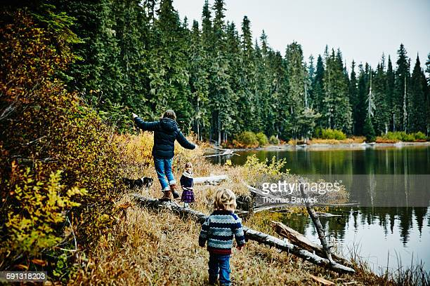 Family walking along shoreline of lake