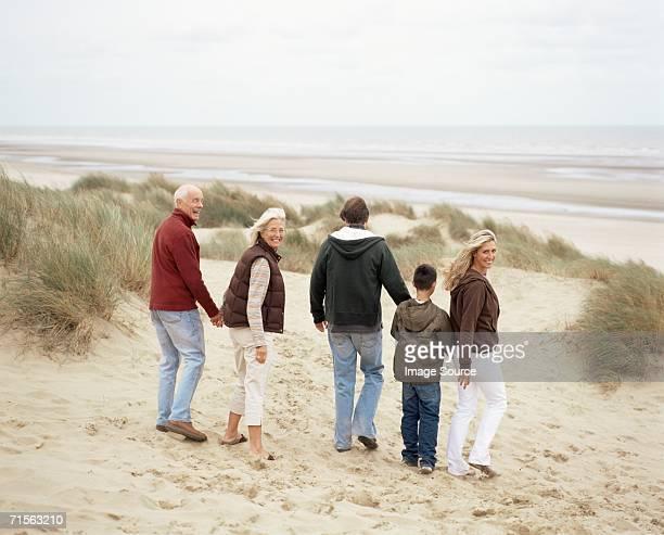 Família caminhar ao longo da praia