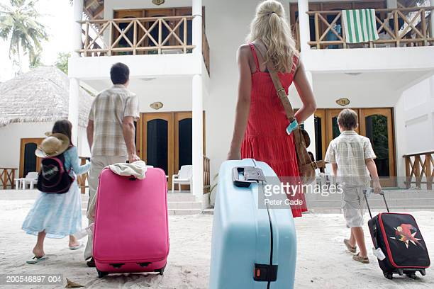 Family walking at resort with suitcase, rear view