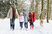Family Walking Dog Through Snowy Woodland