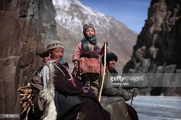 Family walking down frozen river, Zanskar