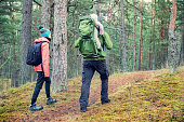 family walking forest trail with baby in child carrier on father's back