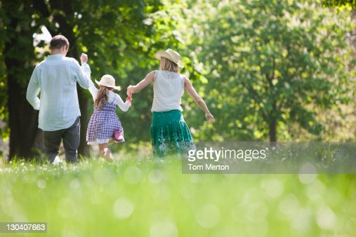 Family walking hand-in-hand in park : Stock Photo