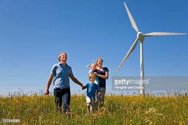 Family walking in field by wind turbine