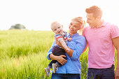 Family Walking In Field Carrying Young Baby Son Smiling