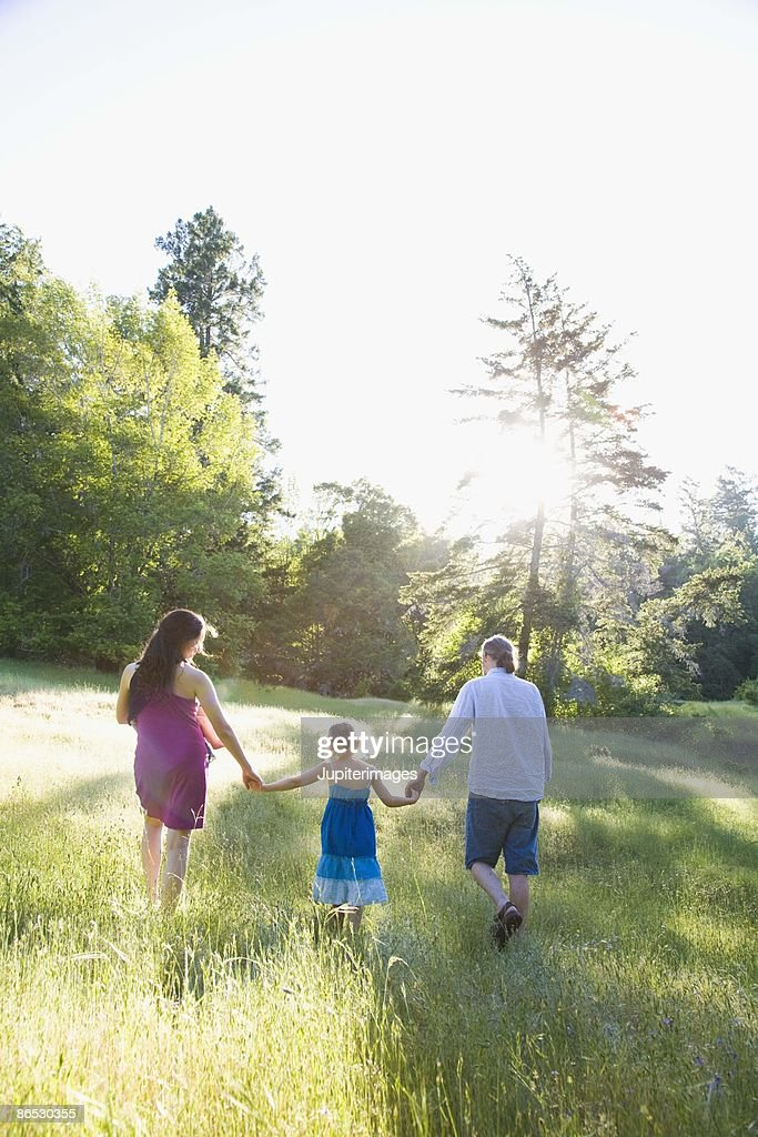 Family walking in grass and sunshine : Stock Photo