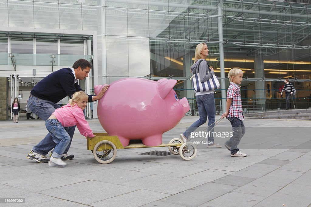 family walking in town with giant piggy bank : Foto stock