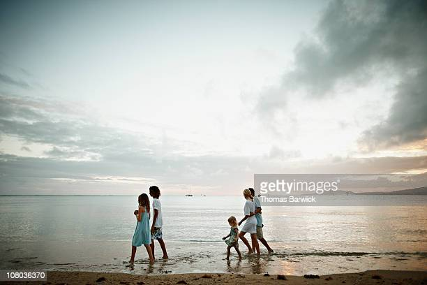Family walking in water on beach at sunset