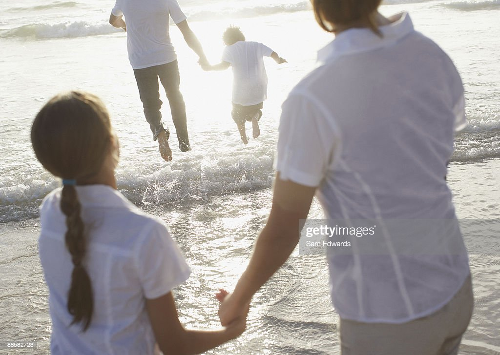 Family walking in waves at beach : Stock Photo