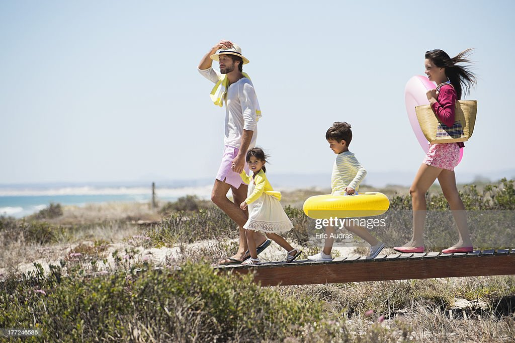 Family walking on a boardwalk on the beach : Stock Photo