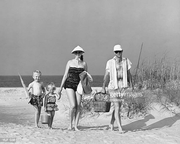 Family walking on beach, carrying fishing poles and portable cooler