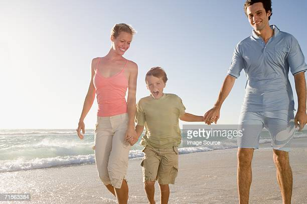 Family walking on beach in the wind
