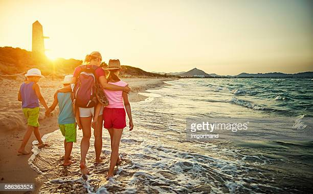 Family walking on beach on sunset