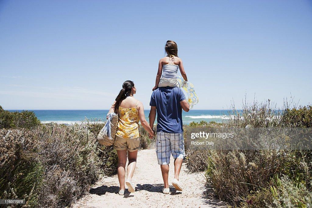 Family walking on beach path toward ocean : Stock Photo