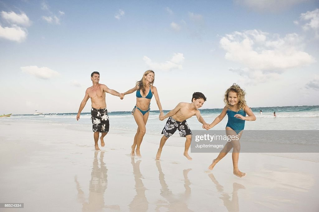 Family walking on beach : Stock Photo