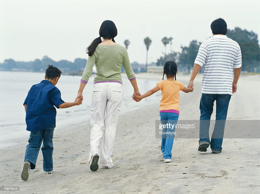 Family walking on beach, rear view : Stock Photo