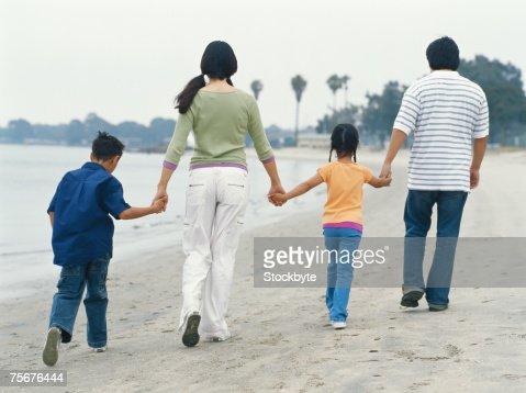 Family walking on beach, rear view : Stock Photo