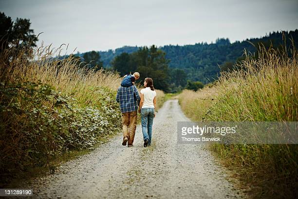 Family walking on dirt road rear view