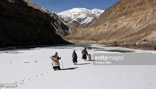Family walking on ice down frozen river, Ladakh