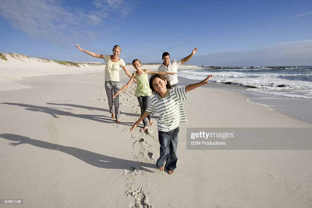 Family walking on the beach : Stock Photo