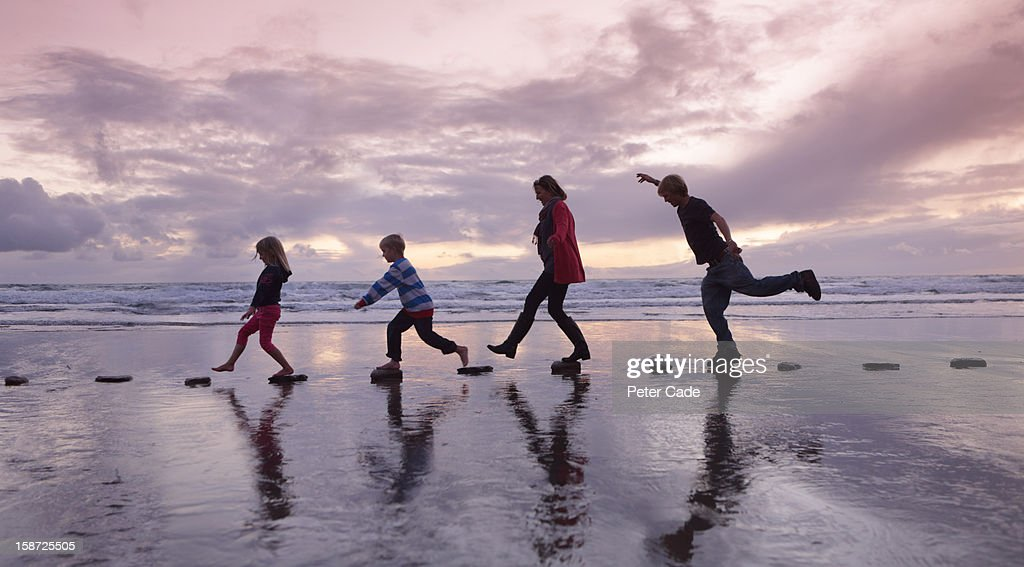 Family walking over stepping stones on beach : Stock Photo