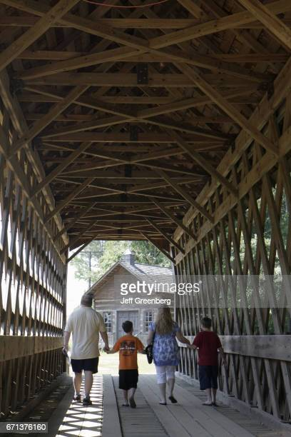 A family walking through a covered bridge at the Pioneer Museum of Alabama