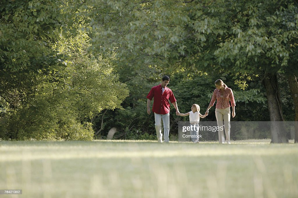Family walking through park : Stock Photo