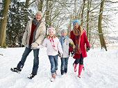 Family Walking Through Snowy Woodland